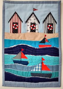 sample for a day at the seaside with beach huts and boats